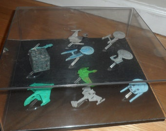 collection of star trek ships on stands and  have a plexiglass case over them will refund ship overages