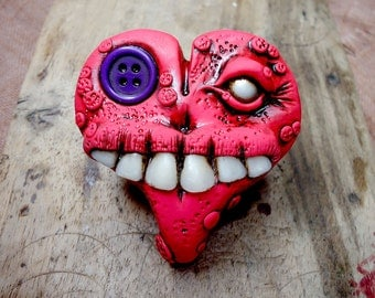 Red monster heart with human teeth and asymmetric eyes: one pearl and one purple button. (Brooch or magnet)