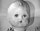 unusual doll head on display art photo, creepy doll with miniatures, funky art photography, weird doll decor