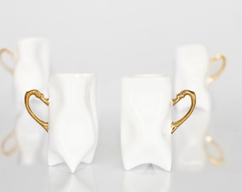 Set of four porcelain white and gold cups. Porcelain mugs for coffee or tea.