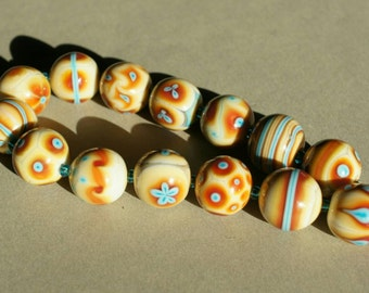 Handmade lampwork bead set in beige/yellow, blue and red by Flamejewels.