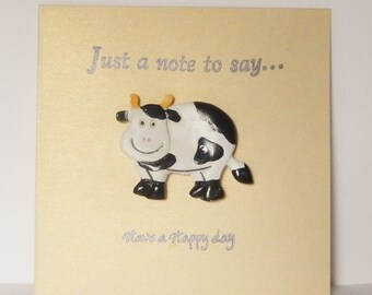 Gold greeting card with a black and white clay cow, that says Just a note to say, Have a happy day, Special occasion card