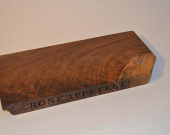 BONE APPETEET! is laser engraved on one edge of a 12 3/8 x 5 3/4 x 1 inch Oregon black walnut slab