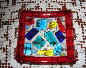 Small square glass dish set with multicolored glass pieces,and a red glass border