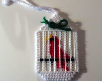 Handmade needlepoint of a cardinal in a cage.