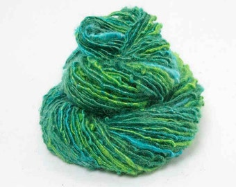 Handspun Single. Kid Mohair Corespun in deep green with turquoise accents
