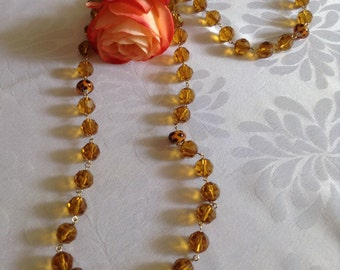 Amber crystal and spotted glass long necklace with matching trapeze earrings. Hand chained on gold plate wire.
