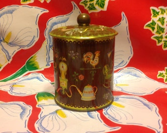 Vintage lidded cylindrical tin with country designs-England