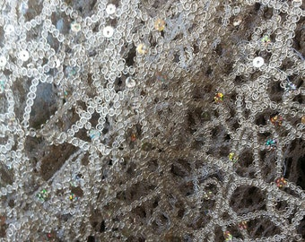 Taupe fancy embroidered lace. Sold by the yard.