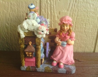 A Charming Animated Musical Figurine with a Girl, Cat and Mice.
