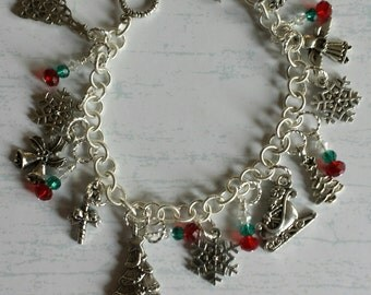 Christmas charm bracelet with trees, snow flakes and more.  Red and green beads also.