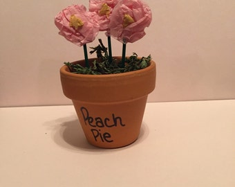 Small potted place holder with tissue paper flowers.