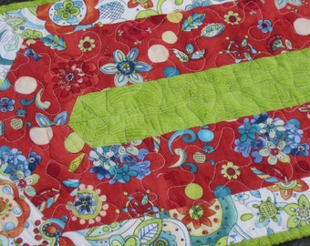 Modern quilted table runner in red, lime green and blues.