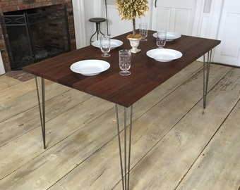 Black walnut dining table, mid century modern style featuring hairpin legs.