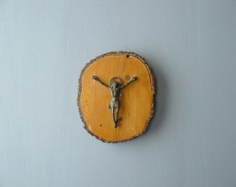 Vintage crucifix. Brass Jesus on the cross on wood. Religious wall decoration