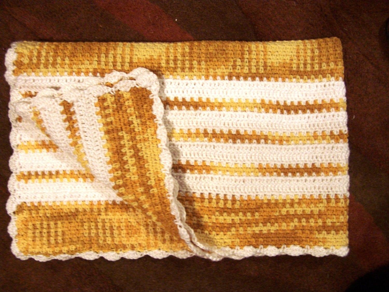 Crochet baby blanket in variegated yellow yarn and white yarn