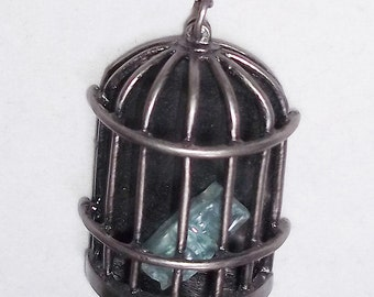 """Bird cage necklace made from """"It's a Mad, Mad, Mad, Mad World"""" car glass."""