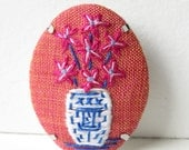 Art hand embroidery willow pattern china pottery vase with pink blue and white flowers.