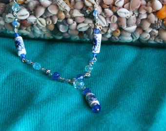 Blue beaded necklace with ceramic bead with flower detail