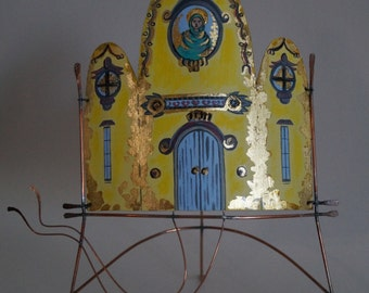 A free standing sculpture which is a beautifully hand painted church with gold leaf.