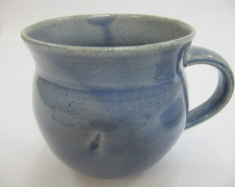 Teacup and saucer,handmade,wheelthrown made from white highfired stoneware  with a blue glaze,the cup and saucer have a sea shell imprints .