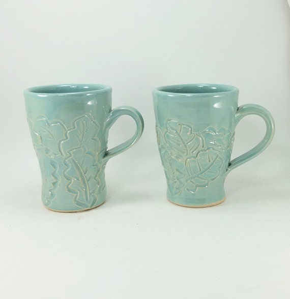 pair of light green mugs with leaves sold together