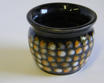 Black wheel thrown pot with a White and Orange Dot pattern over all.