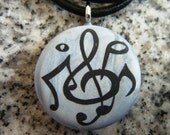 Magic Symphony hand carved on a polymer clay blue/grey pearl color background. Pendant comes with a FREE Necklace