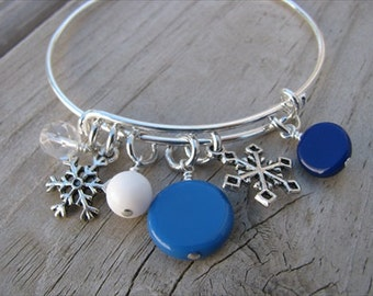 Snowflake Bangle Bracelet- Adjustable Bangle Bracelet with snowflake charms and glass beads in shades of blues, clear, and white