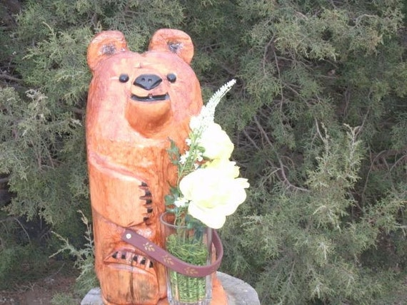 Chainsaw bear carving holding flowers by cactusflatscarvings