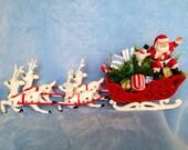 Vintage kitsch plastic Santa in sleigh with reindeer