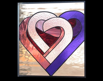 stained glass panel of two hearts is pink purple and beige