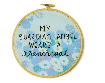 my guardian angel wears a trenchcoat embroidery hoop wall art