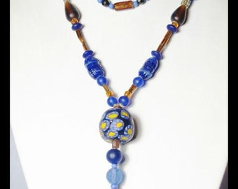 Extra Long 1920's style necklace of blue and old gold colored glass beads.  Featuring a replica Trade Bead and beaded tassel.  One of a Kind