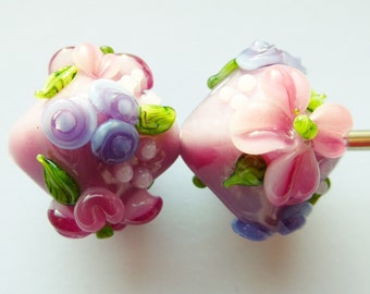 Glass lampwork bead set in pink with raised flower decoration.