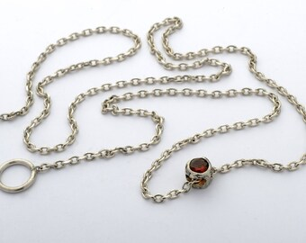 Silver pendant with garnet.