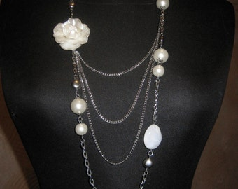 White long necklace with a flower.