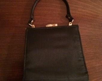 Vintage small black 1950's handbag with kiss lock closure.