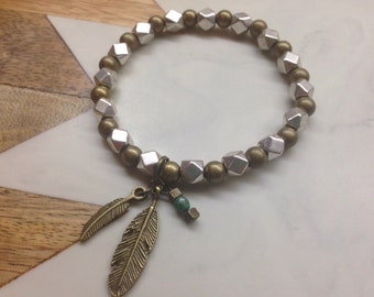 Beaded bracelet with hanging feather detail.