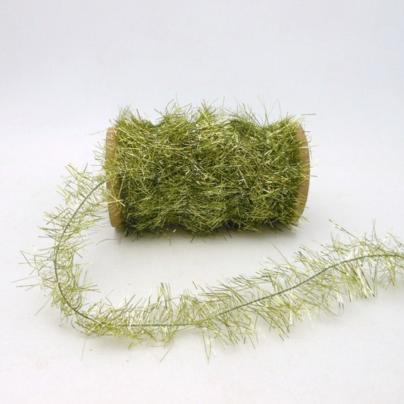 Light green tinsel garland on wooden spool by