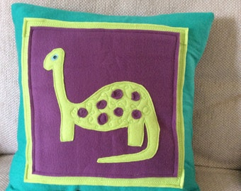 Handcrafted dinosaur cushion or pillow in soft, colourful, cuddly fleece and felt materials.