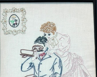 Antique pair of 2 early 1900s Augusta Maine Adams Stores unusual embroidery fabric art of odd romantic Victorian couple framed under glass