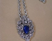 Oval vintage silver tone pendant necklace with blue center stone
