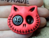 Skull cat in red with a black button in his eye. Brooch, keychain, pendant or magnet (you choose)