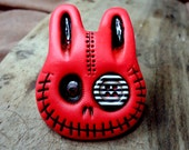Rabbit skull in red with a striped button in his eye. Brooch or magnet (you choose)