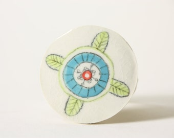 modern flower handmade porcelain magnet in scandinavian style, white with turquoise blue, chartreuse green, and coral red