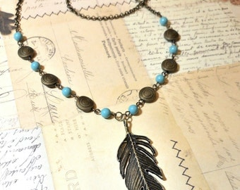 Antique Bronze Feather and Turquoise Beaded Necklace.  Large Bronze Feather is accented by Swarovski turquoise beads on a 24 inch necklace.