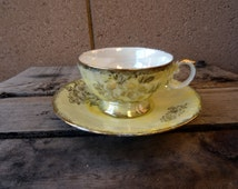 Tea Cup with Saucer, Silver Company National. Nasco China. Made in Japan Yellow Pearlized With Gold Floral And Rimed