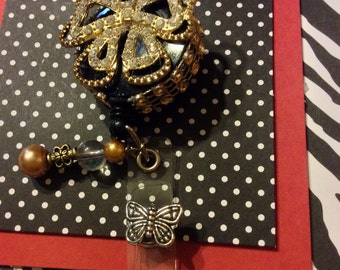 Gold tone bow retractable badge holder