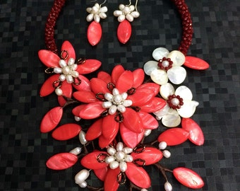 Red flowers made of shells. To make your dress look more prominent.